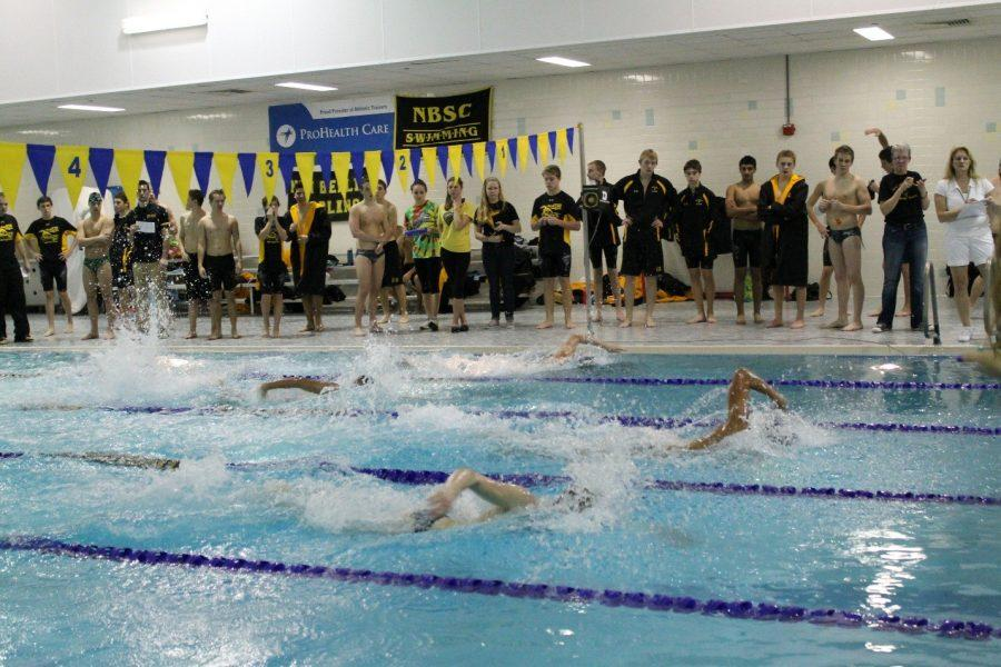 The+Marlins+watch+intently+as+Zach+Solie+swims+in+the+50+freestyle.+He+took+second+place%2C+beat+out+by+a+senior+from+Greenfiled.
