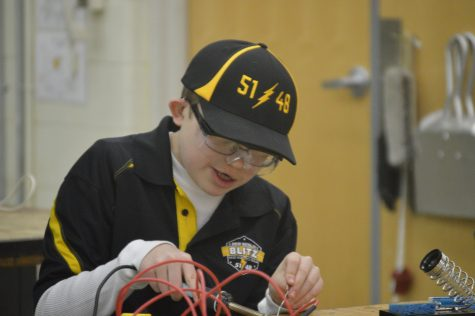 Mason Primus, demonstrating how to solder two wires together at the STEM fair